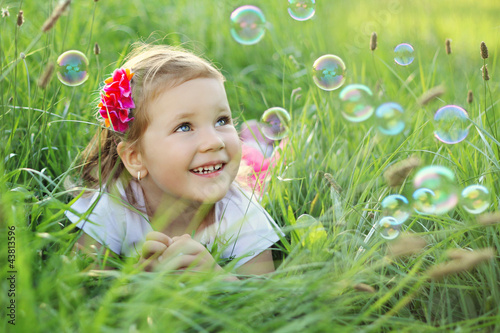 Happy little girl playing with bubbles