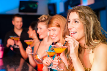People in club or bar drinking cocktails