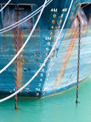Depth scale on bow of anchored ship in grungy blue