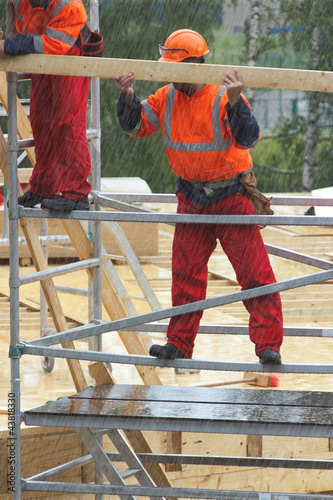 Construction worker is holding a wooden board in rainy day
