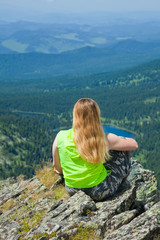 Woman sitting on mountain peak