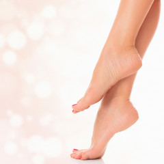 Female feet on pastel  background with circles and copyspace