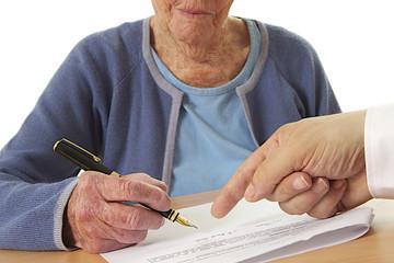 Femme âgée signant un contrat