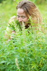 Happy woman   at cannabis plant