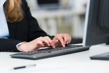 junge frau schreibt auf einer computertastatur