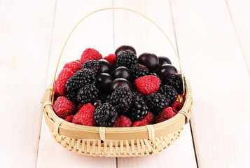 Ripe raspberries and brambles in basket on wooden table