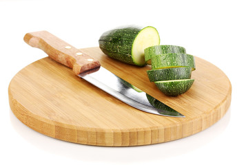 Sliced zucchini on chopping board isolated on white