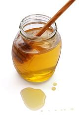Honey with wood stick, isolated on white background