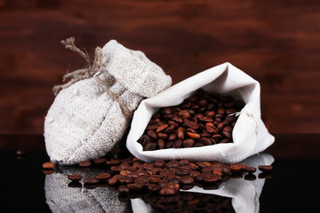 Coffee beans in canvas sack isolated on wooden