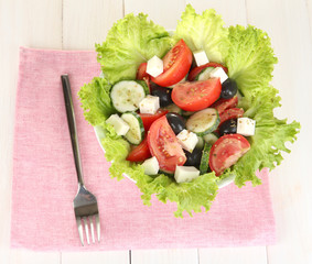 tasty Greek salad on white wooden background