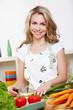 Frau beim Gemüse schneiden in Küche