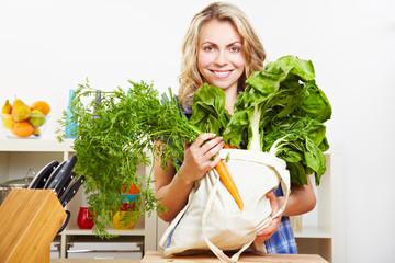 Frau in Küche mit Einkaufstasche