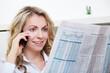 Frau telefoniert beim Zeitungslesen