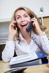 Lachende Frau mit zwei Telefonen