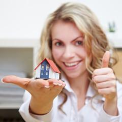 Frau mit Haus hält Daumen hoch