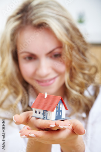 Frau hält Haus auf Händen