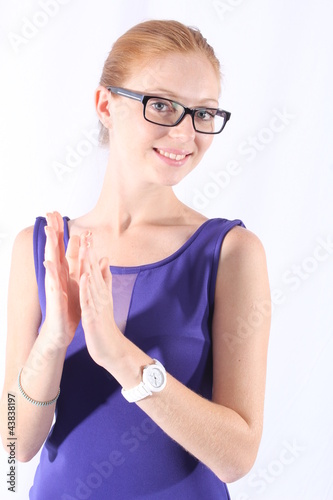 Attractive young woman with eyeglasses clapping her hands