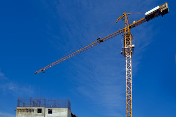 Construction crane against the blue sky and the house under cons