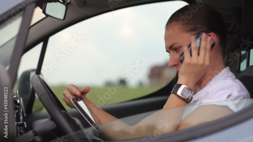Young businesswoman with tablet and phone in traffic jam
