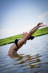 beautiful young woman bathing in a lake