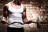 Fototapety Muscular guy doing exercises with barbell