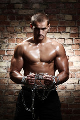 Muscular man with chains on his wrists