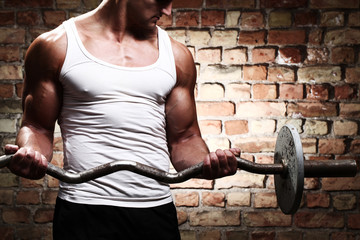 Muscular guy doing exercises with barbell