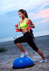 Woman doing fitness exercises with bosu ball
