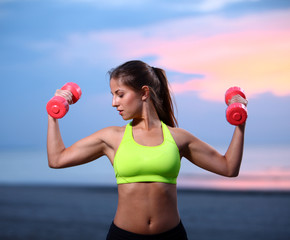 Woman doing exercises with dumbbells on the beach