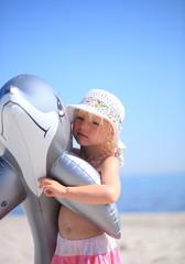 kleines Mädchen mit Schwimmtier am Strand