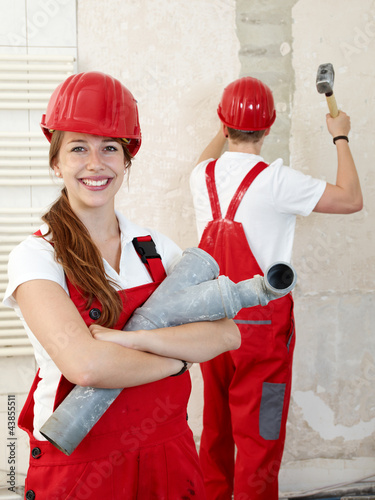 Young worker fixing up a house, working in a building lot