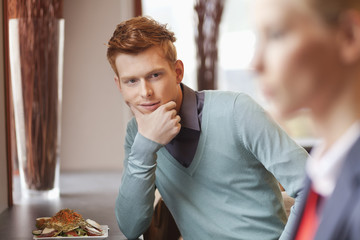 Man in a restaurant looking at a businesswoman