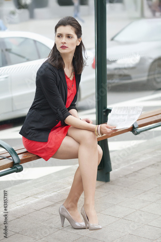 Woman waiting at the bus stop and holding a newspaper