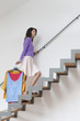Woman moving up stairs carrying clothes