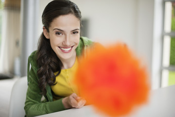 Happy woman holding a feather duster