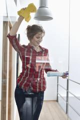 Woman cleaning glass door