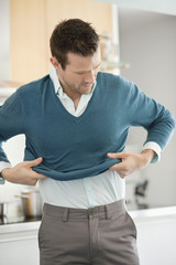 Man putting on sweater in the kitchen