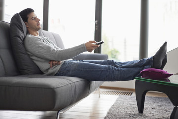 Man reclining on a couch and watching television