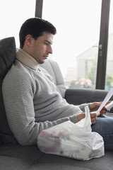 Man sitting on a couch reading medical prescription