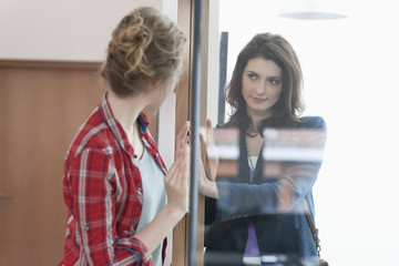 Two female friends looking at each other through a glass door