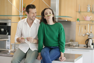 Couple playing with green bean in the kitchen