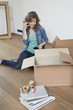 Woman talking on a mobile phone near cardboard boxes