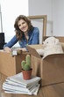 Woman sitting near cardboard boxes and smiling