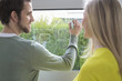 Woman looking at an architect drawing a design on the window glass