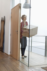 Woman carrying a cardboard box at home