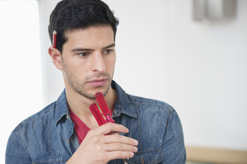 Technician holding screwdrivers and thinking
