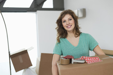 Woman carrying cardboard box and smiling
