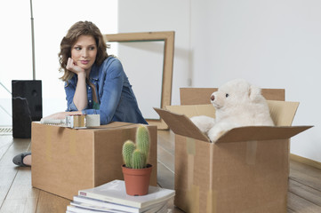 Woman leaning on a cardboard box and looking at a teddy bear