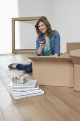 Woman sitting near cardboard boxes and using a mobile phone