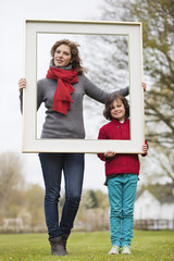 Woman and her son holding a picture frame in a park